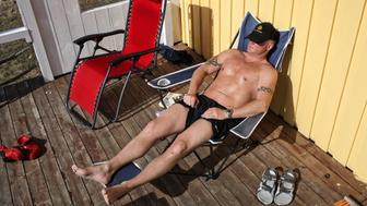 BASTOY ISLAND, HORTEN, NORWAY - APRIL 11:  An inmate which gave the fake name of Niels, 36-years-old sentenced to sixtheen years and a half for murder and narcotics related crime is seen sun bathing in front of the wooden cottage where he lives in Bastoy Prison on April 11, 2011 in Bastoy Island, Horten, Norway. Bastoy Prison is a minimum security prison located on Bastoy Island, Norway, about 75 kilometers (46 mi) south of Oslo. The facility is located on a 2.6 square kilometer (1 sq mi) island and hosts 115 inmates. Arne Kvernvik Nilsen, governor of the prison, leads a staff of about 70 prison employees. Of this staff, only five employees remain on the island overnight.  Once a prison colony for young boys, the facility now is trying to become 'the first eco-human prison in the world.' Inmates are housed in wooden cottages and work the prison farm. During their free time, inmates have access to horseback riding, fishing, tennis, and cross-country skiing. (Photo by Marco Di Lauro/Reportage by Getty Images)