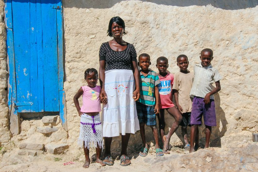 St. Abel Pierre stands in front of her house with some of her grandchildren.
