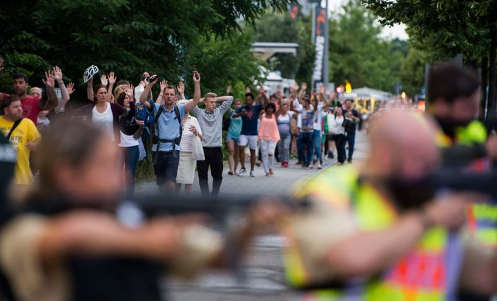 Police escorts evacuate people from ashopping mall in Munich on Fridayfollowing a shooting.