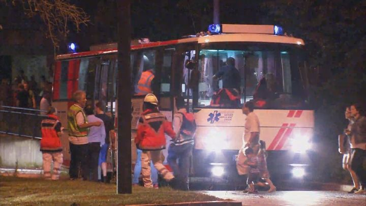A screen grab taken from video footage shows people being evacuated onto a bus following a shooting rampage at the Olympia sh