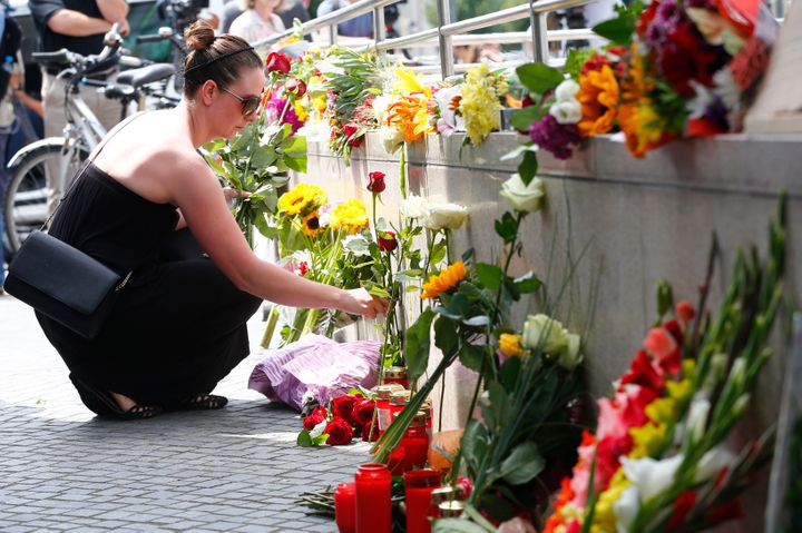 A women places flowers near the Olympia shopping mall, where yesterday's shooting rampage started, in Munich, Germany July 23