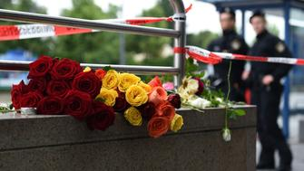 Police officers stand near flowers commemorating victims at the entrance of the subway station near the shopping mall Olympia Einkaufzentrum OEZ in Munich on July 23, 2016, a day after a gunman went on a shooting rampage, killing eight people in a suspected terror attack.  The southern city was in lockdown after the shootings, which saw panicked shoppers fleeing the Olympia mall as armed anti-terror police roamed the streets in search of assailant.  / AFP / Christof Stache        (Photo credit should read CHRISTOF STACHE/AFP/Getty Images)