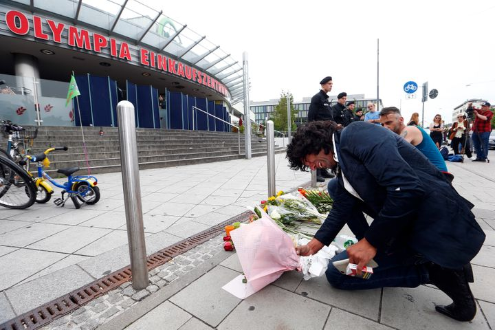A man places flowers outside the Olympia shopping mall in Munich, where a German-Iranianteenager killed nine people on