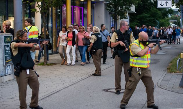 Police officers guard with guns as other officers escort people from inside the shopping center as they...