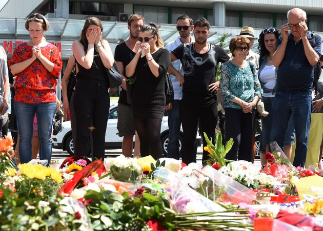 People mourn at a memorial of candles and flowers on July 24, 2016 in front of the Olympia Einkaufszentrum...