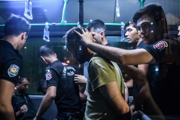 Turkish police detain a Turkish soldier in Istanbul on July 16 who allegedly took part in a military...