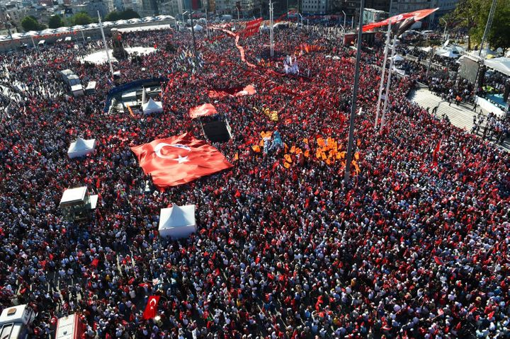 Thousands of supportersof various Turkish political parties hold Turkish flags and pictures of Mustafa Kemal Ataturk, t