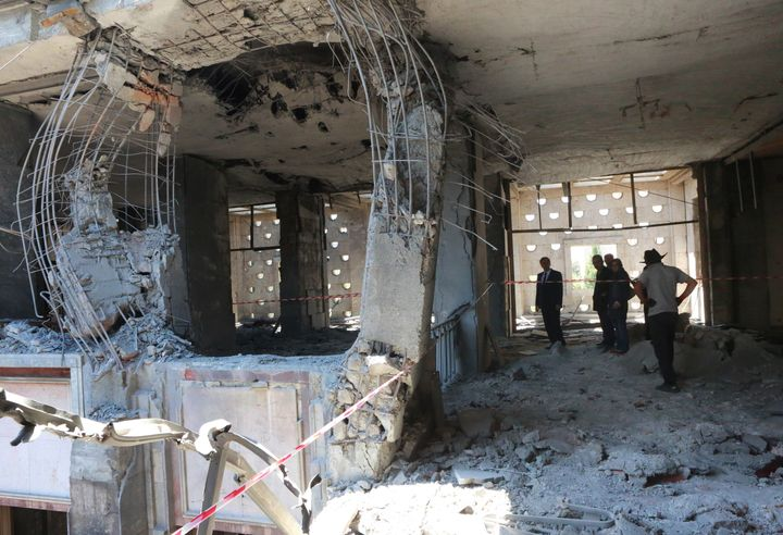 People inspect damage on July 16 after Turkey's parliamentary complexwas bombed by rebel-flown jets in Ankara.At