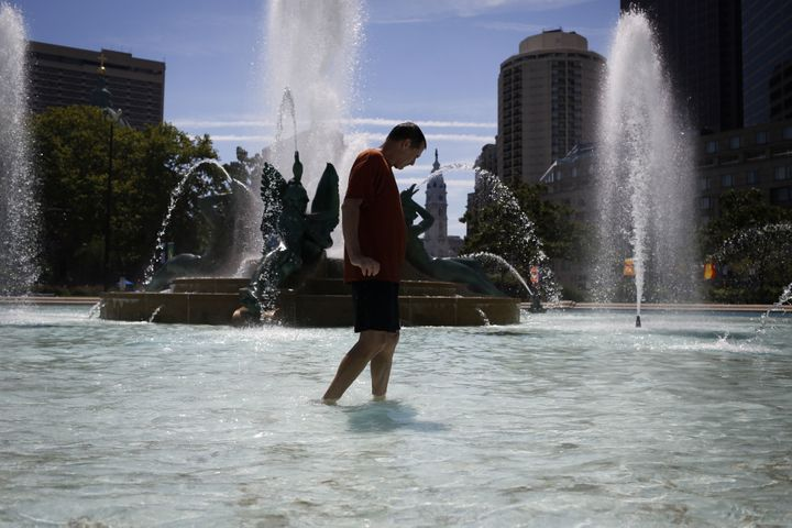 A man cools off by walking through a fountain in the Center City neighborhood in Philadelphia.