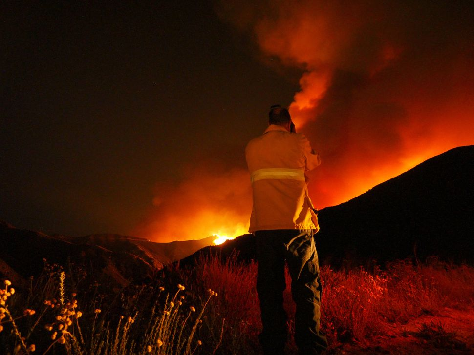 An emergency responder watches the fire in the distance.