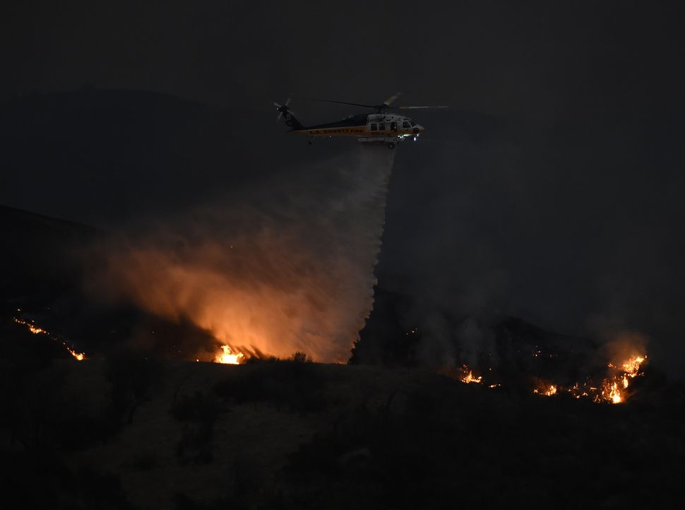 A firefighting helicopter drops water on the blaze.