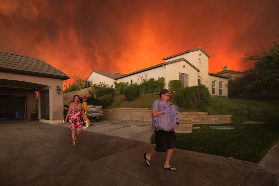 Residents flee their home as flames continue to spread.