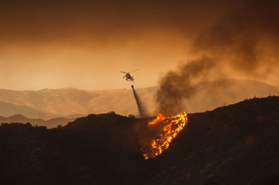 A firefighting helicopter drops water on a flaming hillside.
