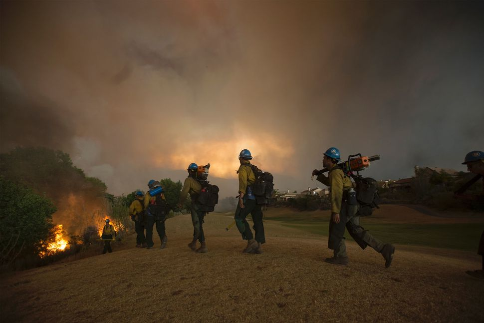 Firefighters of the Texas Canyon Hotshot crew work to control the blaze near a residential golf course.