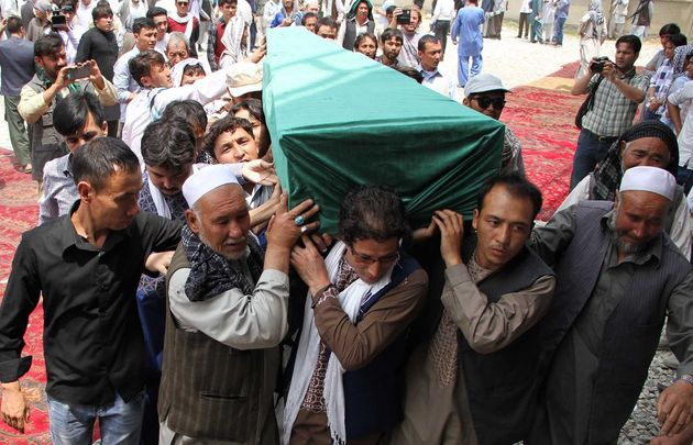 Afghan Shiites carry the coffin of a victim killedwhen a suicide attacker detonated explosive belts...