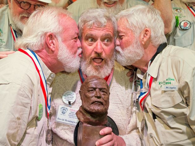 Dave Hemingway receives smooches from Charlie Boise, left, and Wally Collins, right, after winning the...