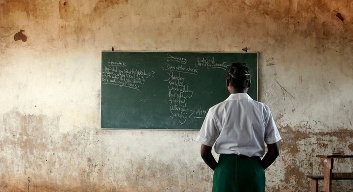 A young girl reads the day's lessons at a school near Xia Xia, Mozambique on April 26, 2005. Chi