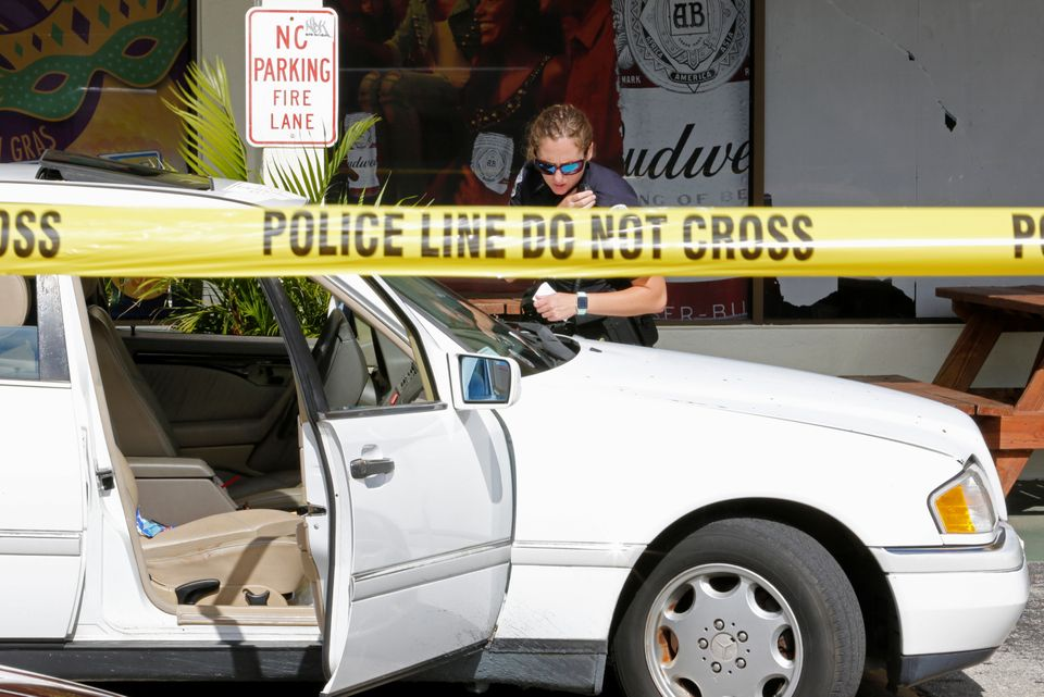 A Fort Myers police officers examines a vehicle in the parking lot of Club Blu.