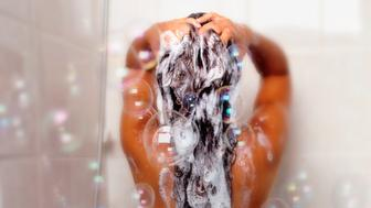 Naked woman showering in bathroom, rear view