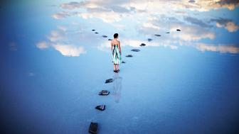 Woman standing at fork in stone pathway in calm lake with clouds reflecting in water
