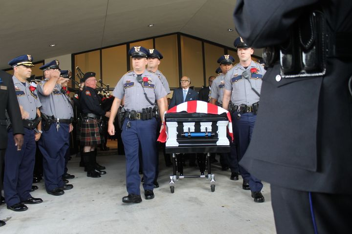 The casket for slain Baton Rouge police officer Montrell Jackson departs his funeral on Monday.