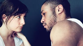 Portrait of a young couple sitting face to face in a thoughtful mood.