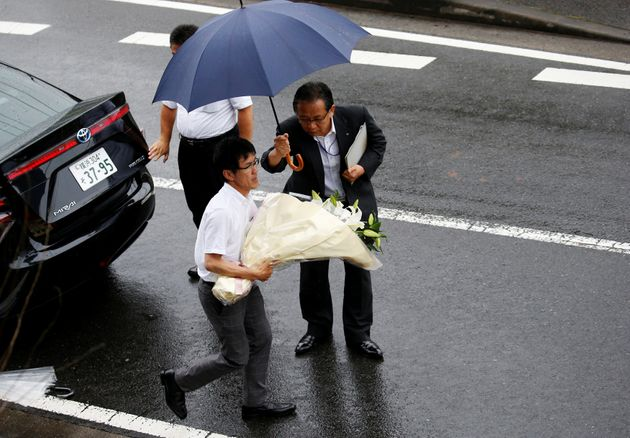 A prefecture government staff member carries flowers to mourn victims of the