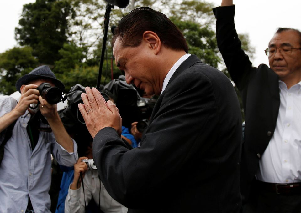 Governor of Japan's Kanagawa prefecture Yuji Kuroiwa (C) prays to mourn victims as he visits at a facility for the disabled,