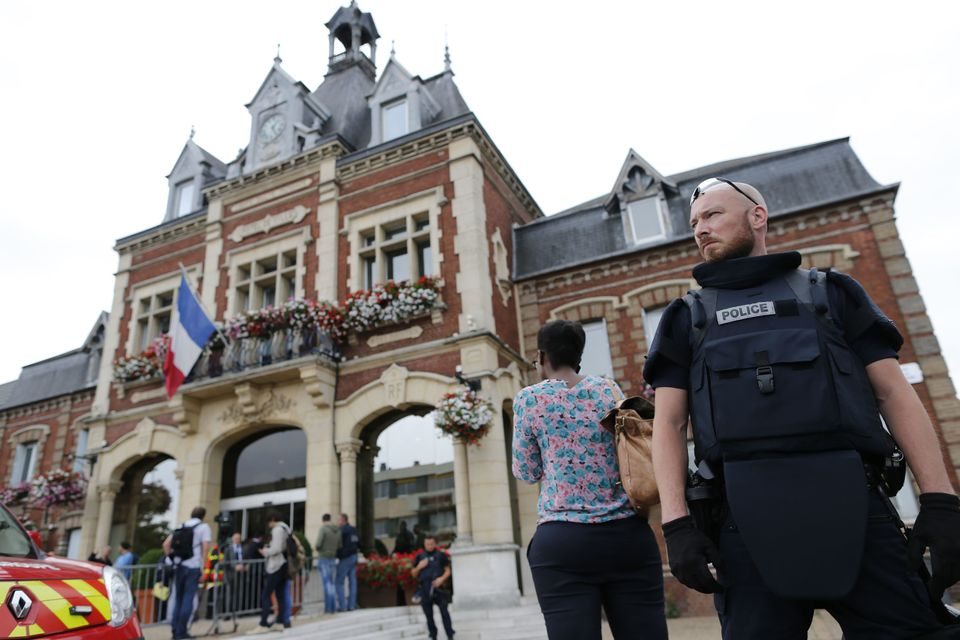A French police officer stands guard by Saint-Etienne-du-Rouvray's city hall following a hostage-taking at a church in Saint-