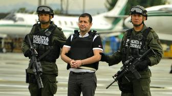 Colombian drug trafficker Daniel Barrera (C) aka 'El Loco' is escorted by policemen before being deported to the United States at the Antinarcotics Police Airport on July 9, 2013  in Bogota. Barrera is considered as Colombias most important drug lord of the past decade. AFP PHOTO/LUIS ACOSTA        (Photo credit should read LUIS ACOSTA/AFP/Getty Images)