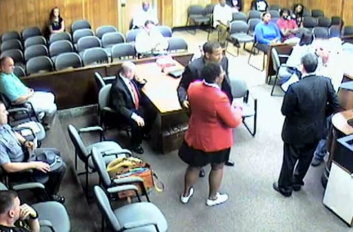 In this screenshot of security footage, attorney Andrea Burton is being taken into custody by bailiffs after refusing to remo