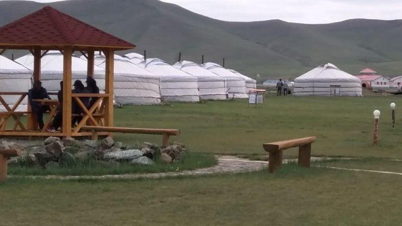 Tourists lounge in a <i>ger</i> camp pavilion