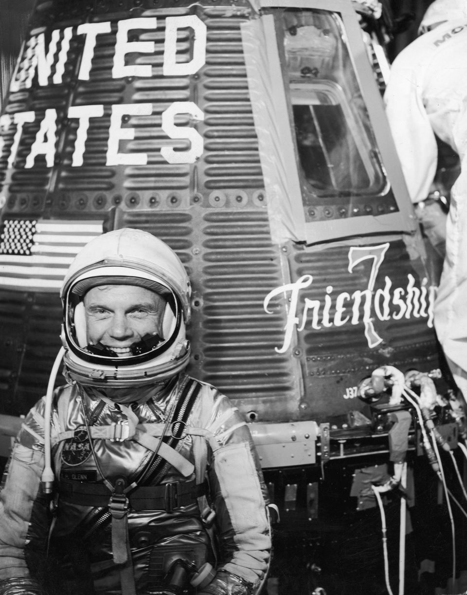 23rd January 1962: American astronaut John Glenn Jr smiles while wearing a spacesuit and helmet in front of the Mercury Atlas