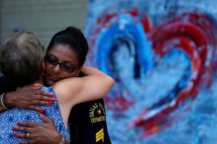 A woman hugs a Dallas police officer at a makeshift memorial at police headquarters following the multiple police shootings i