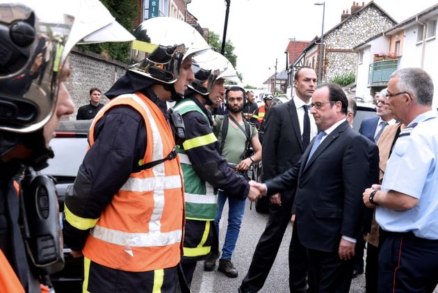 Hollande shakes hands with French firemen as he arrives in