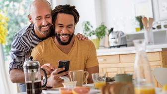 Smiley homosexual couple using smart phone at dinner table