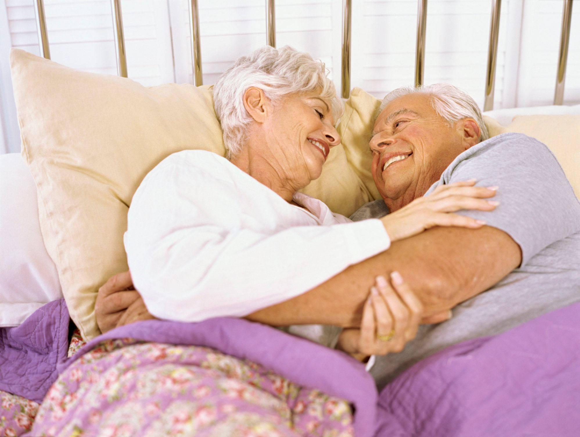 High angle view of a senior couple lying on the bed, hugging
