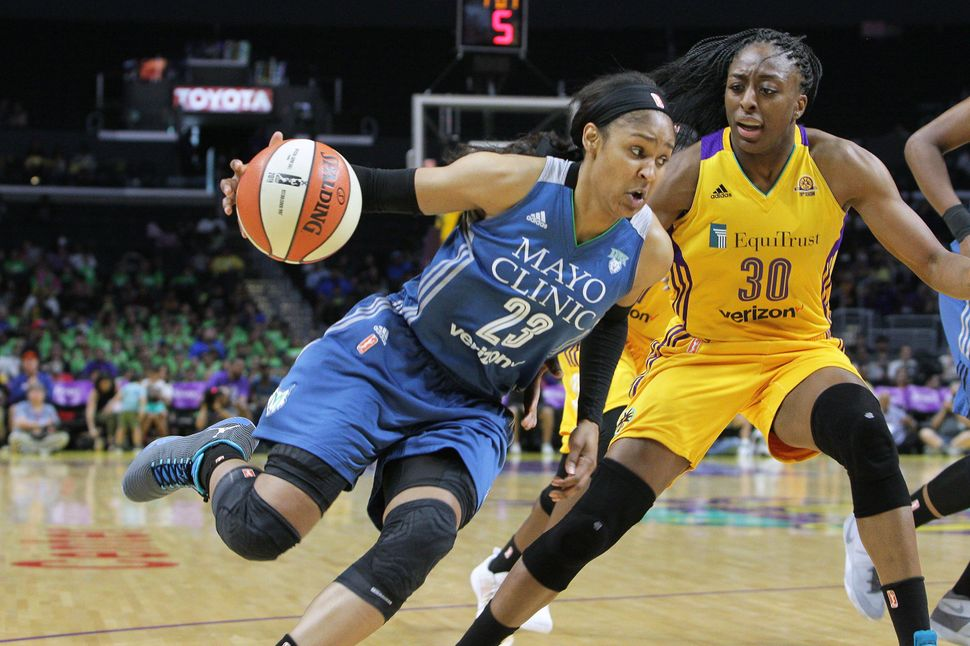 Maya Moore (#23) of the Minnesota Lynx handles the ball against Nneka Ogwumike (#30) of the Los Angeles Sparks during a WNBA