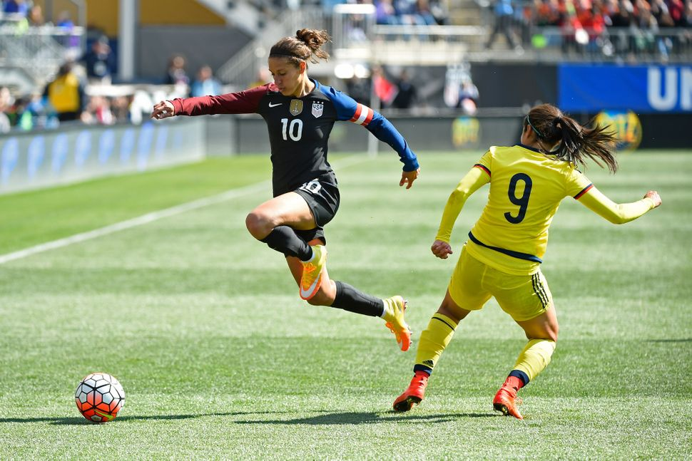 Carli Lloyd (#10) of the United States leaps over the defense of Orianica Velasquez (#9) of Colombia during the second half o