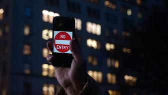 NEW YORK, NY - FEBRUARY 23: A protestor holds up an iPhone that reads, 'No Entry' outside of the the Apple store on 5th Avenue on February 23, 2016 in New York City. Protestors gathered to support Apple's decision to resist the FBI's pressure to build a 'backdoor' to the iPhone of Syed Rizwan, one of the two San Bernardino shooters. (Photo by Bryan Thomas/Getty Images)
