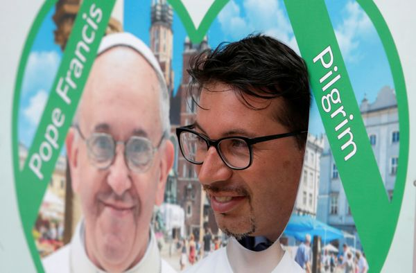 A pilgrim poses next to a picture of Pope Francis at the main square during World Youth Day in Krakow, Poland, July 26, 2016.