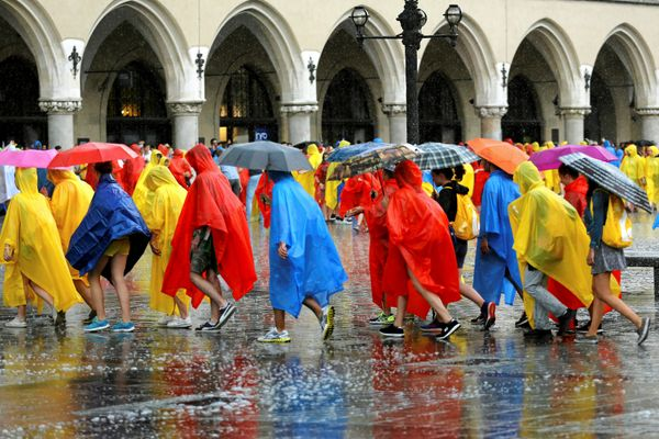 Pilgrims covered in rain coats walk during heavy rain on World Youth Day at the Main Square in Krakow, Poland July 26, 2016.