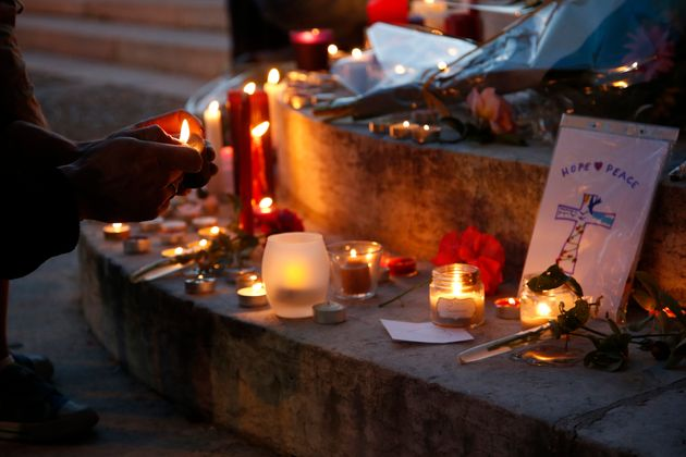 A woman lights a candle to place with flowers and candles at the town hall in Saint-Etienne-du-Rouvray,...