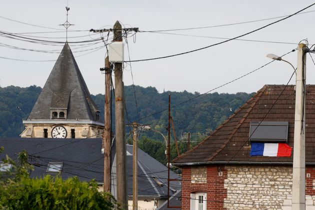 A French flag is seen on a rooftop near the bell tower of the church after a hostage-taking in Saint-Etienne-du-Rouvray...