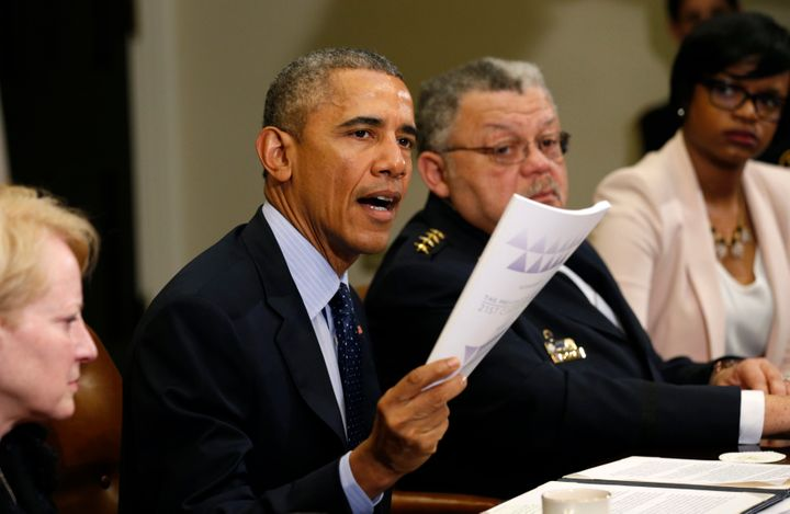 President Barack Obama holds up a copy of the report by the Task Force on 21st Century Policing at the White House in Washington March 2, 2015.