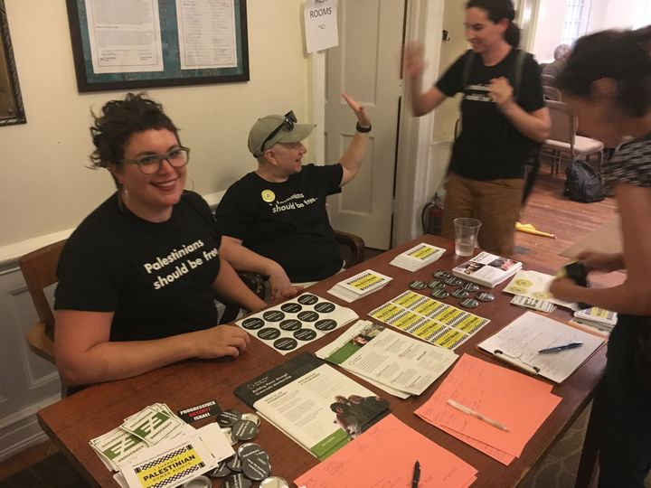 """Rabbi Alissa Wise (left) of Jewish Voice for Peace distributes pamphlets at a panel discussion on Monday. Her shirt says, """"Pa"""