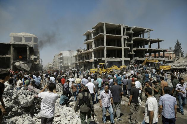 Syrians gather at the site of a bomb attack in Syria's northeastern city of