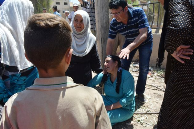 A woman mourns dead relativesinthe northeastern Syrian city of Qamishli near the Turkish...