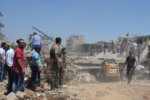 People look for survivors under debris at a damaged site after