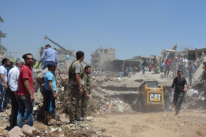 People look for survivors under debris at a damaged site after the attack.